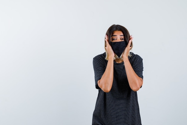 Jeune femme tenant les mains sur les joues en robe noire, masque noir et à la recherche de sérieux. vue de face.
