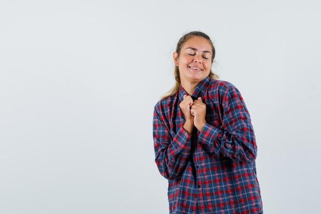 Jeune femme tenant les mains sur la poitrine en chemise à carreaux et à la recherche de calme. vue de face.