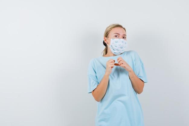 Jeune femme tenant les mains sur la poitrine en t-shirt, masque et ayant l'air effrayé