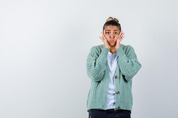 Jeune femme tenant les mains pour faire face, gonflant les joues en chemise blanche et cardigan vert menthe et à l'air amusé
