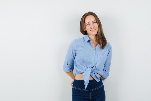 Jeune femme tenant les mains sur son dos en chemise bleue, pantalon et à l'optimiste