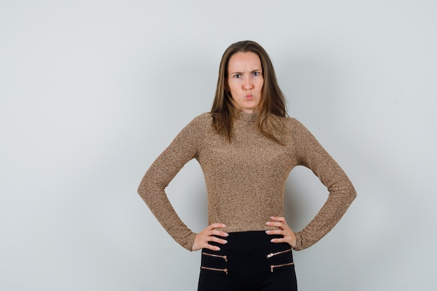 Jeune femme tenant les mains sur la taille en pull doré et pantalon noir et à la surprise