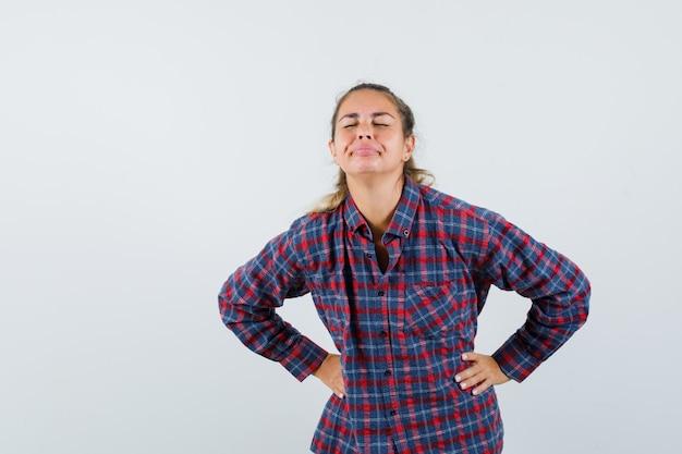 Jeune femme tenant les mains sur la taille tout en fermant les yeux en chemise à carreaux et à la sérieuse