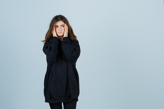 Jeune femme tenant les mains sur les tempes dans un sweat à capuche surdimensionné, un pantalon et l'air fatigué. vue de face.