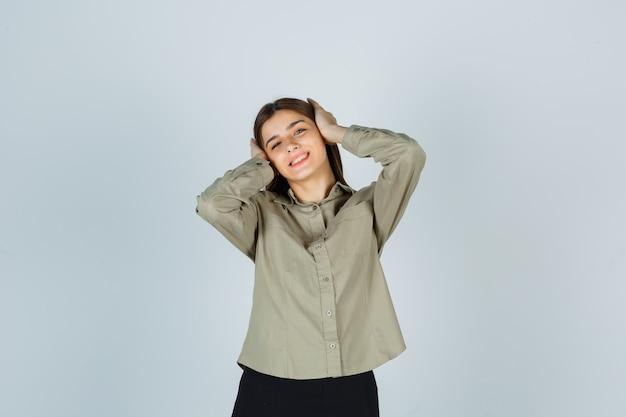 Jeune femme tenant les mains sur la tête en chemise et à la joyeuse