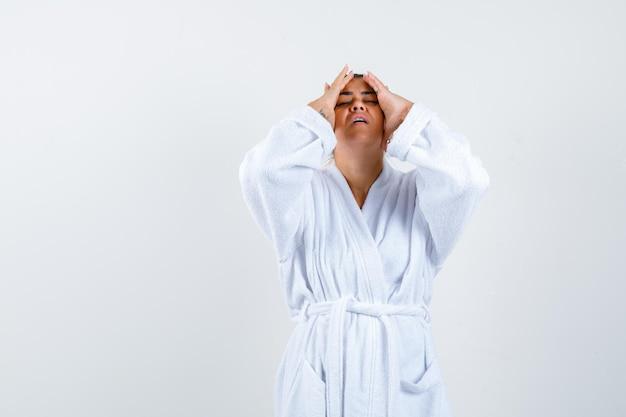 Jeune femme tenant les mains sur la tête en peignoir et à l'air ennuyé