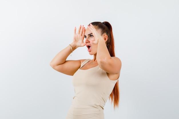 Jeune femme tenant les mains sur la tête pour voir clairement en débardeur beige et à la perplexité, vue de face.