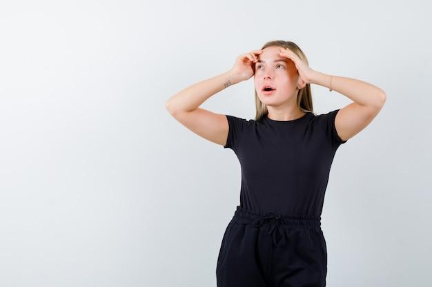 Jeune femme tenant les mains sur la tête en t-shirt, pantalon et regardant à travers, vue de face.