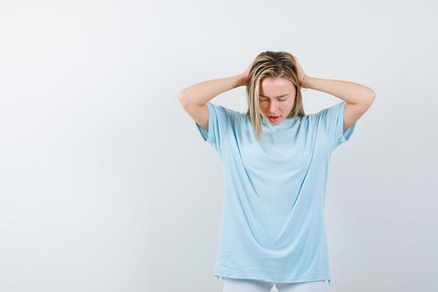 Jeune femme tenant les mains sur la tête en t-shirt et à la recherche d'isolement agacé