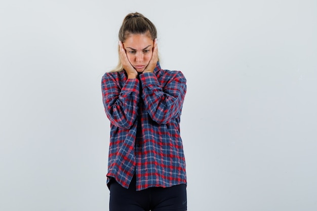 Jeune femme tenant les mains sur le visage en chemise à carreaux et à la pensif