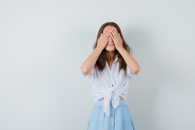 Jeune femme tenant les mains sur les yeux en chemisier, jupe et à excité