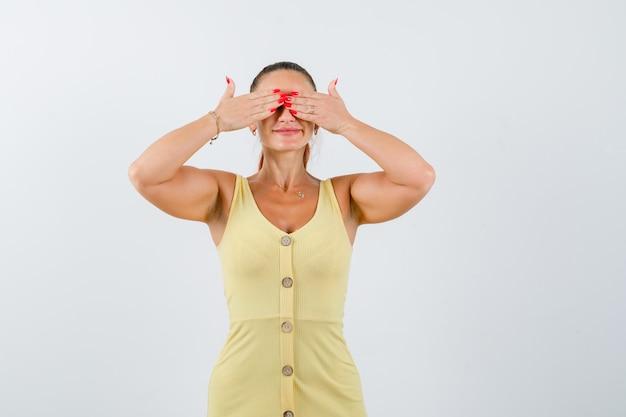 Jeune femme tenant les mains sur les yeux en robe jaune et l'air excité. vue de face.