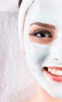 Jeune femme tenant un masque sur le visage dans un salon spa.