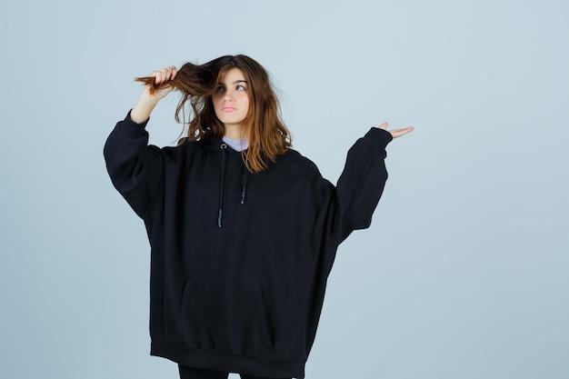 Jeune femme tenant une mèche de cheveux en sweat à capuche surdimensionné, pantalon et à la vue réfléchie, de face.