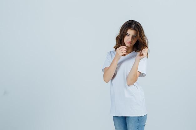 Jeune femme tenant une mèche de cheveux en t-shirt, jeans et à la pensif. vue de face.