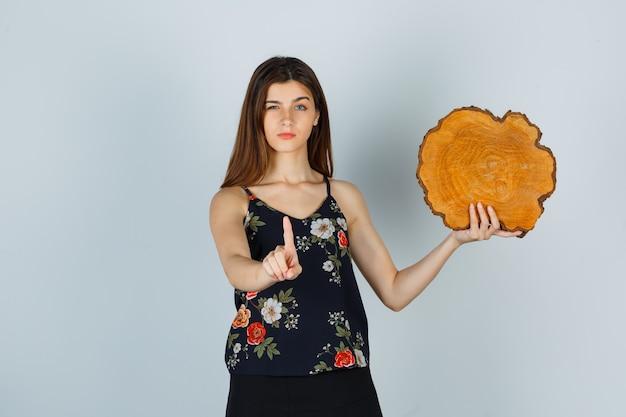 Jeune femme tenant un morceau de bois, montrant la prise d'un geste minute en chemisier, jupe et l'air sérieux, vue de face.