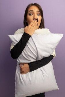 Jeune femme tenant un oreiller choqué couvrant la bouche avec la main