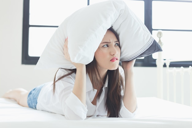 Jeune femme tenant l'oreiller dans la chambre à la maison.