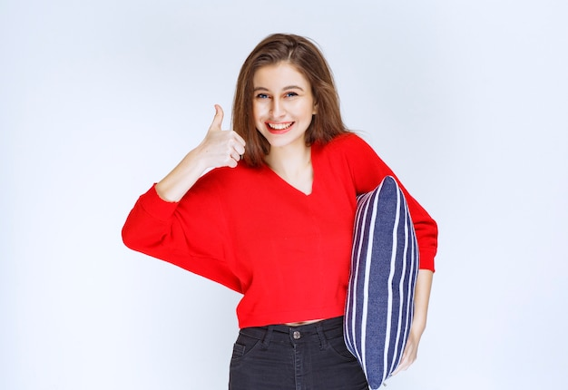 Jeune femme tenant un oreiller rayé bleu et se sentir positif.