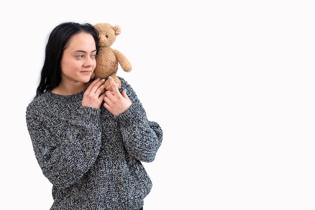 Jeune femme tenant un ours en peluche, isolé sur blanc