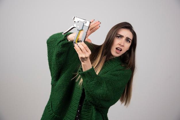 Une jeune femme tenant un outil de travail sur fond gris.