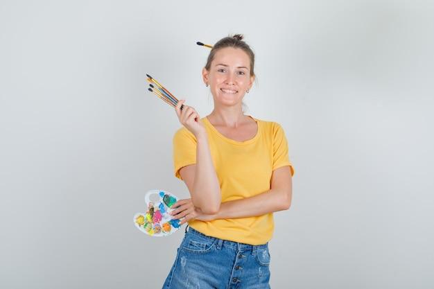 Jeune femme tenant une palette d'art avec des pinceaux en t-shirt jaune, short en jean et à la recherche de bonheur