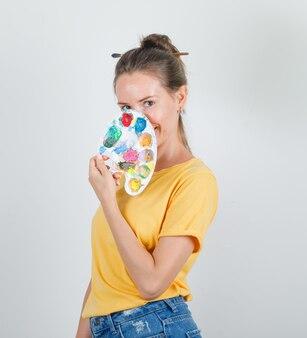 Jeune femme tenant la palette sur le visage en t-shirt jaune, short en jean et à la joyeuse