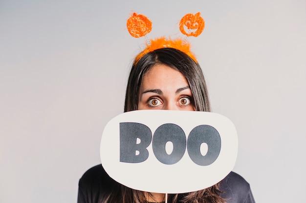 Jeune femme tenant une pancarte boo. portant un costume squelette noir et blanc. concept d'halloween. à l'intérieur. mode de vie