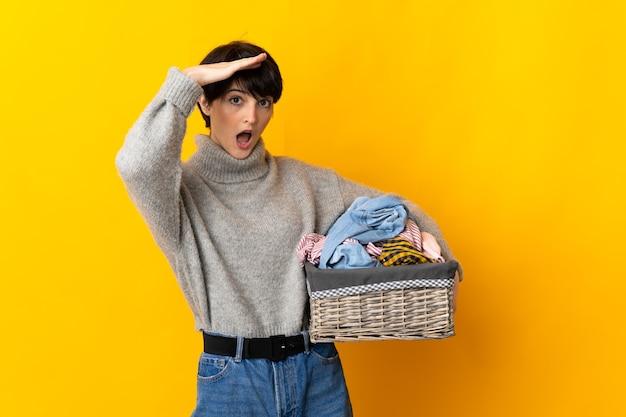 Jeune femme tenant un panier de vêtements faisant un geste de surprise tout en regardant sur le côté