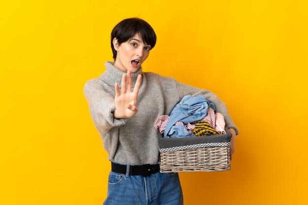 Jeune femme tenant un panier de vêtements heureux et comptant quatre avec les doigts