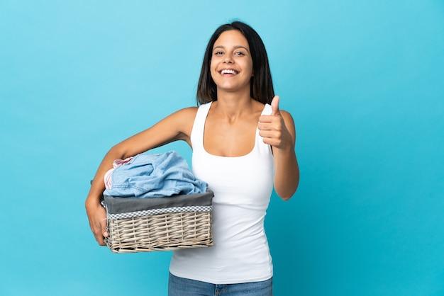 Jeune femme tenant un panier de vêtements sur un mur isolé avec les pouces vers le haut parce que quelque chose de bien s'est passé