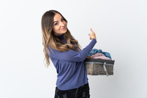 Jeune femme tenant un panier de vêtements posant isolé contre le mur blanc