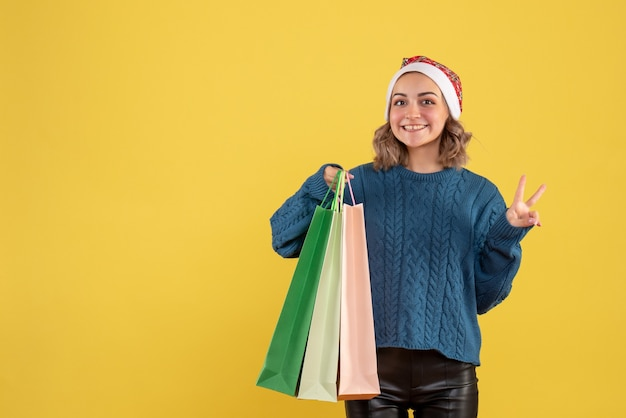 Jeune femme tenant des paquets après le shopping sur jaune