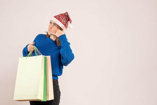 Jeune femme tenant des paquets avec des cadeaux sur blanc