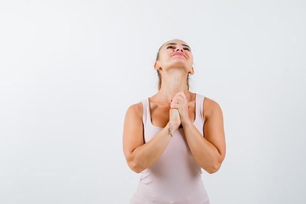 Jeune femme tenant par la main en signe de prière en maillot et à la recherche d'espoir. vue de face.