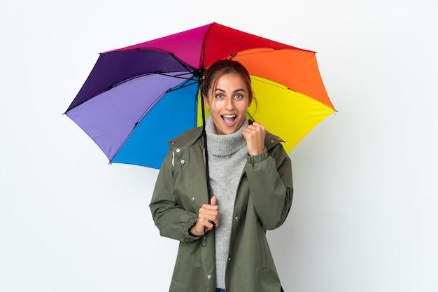Jeune femme tenant un parapluie sur fond blanc célébrant une victoire en position de vainqueur