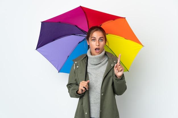 Jeune femme tenant un parapluie isolé sur un mur blanc dans l'intention de réaliser la solution tout en levant un doigt