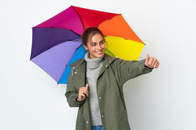 Jeune femme tenant un parapluie isolé sur un mur blanc donnant un geste de pouce en l'air