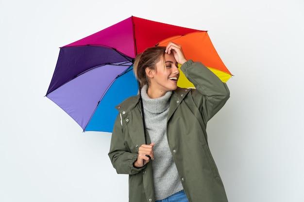 Jeune femme tenant un parapluie isolé sur un mur blanc a réalisé quelque chose et l'intention de la solution