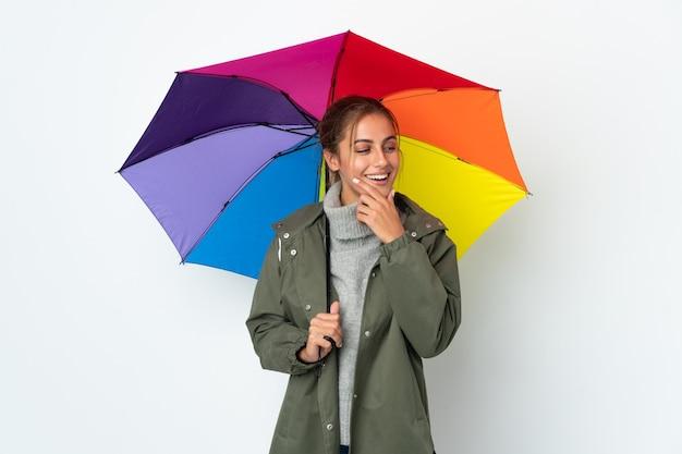 Jeune femme tenant un parapluie isolé sur un mur blanc regardant sur le côté et souriant