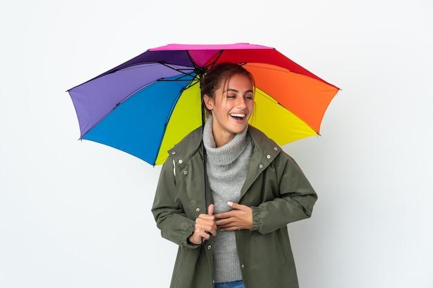 Jeune femme tenant un parapluie isolé sur un mur blanc souriant beaucoup