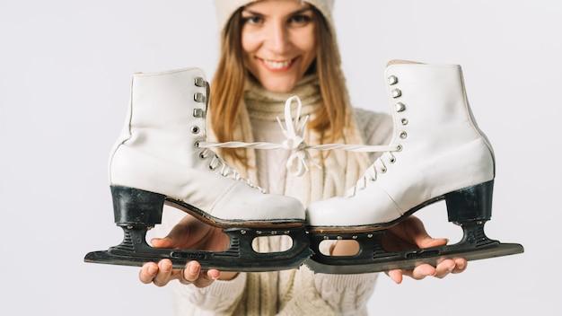 Jeune femme tenant des patins blancs
