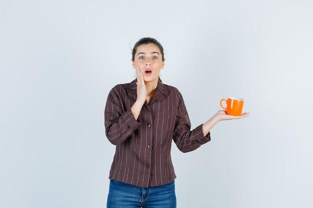Jeune femme tenant la paume sur la joue, gardant la tasse en chemise, jeans et semblant surprise, vue de face.