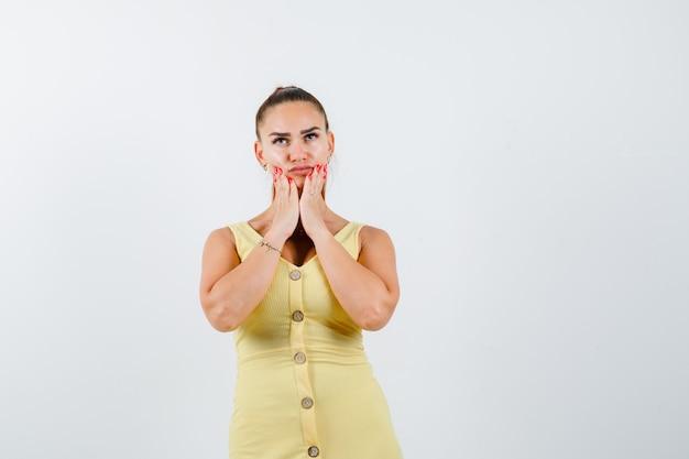Jeune femme tenant les paumes sur le menton en robe jaune et à la vue nostalgique, de face.