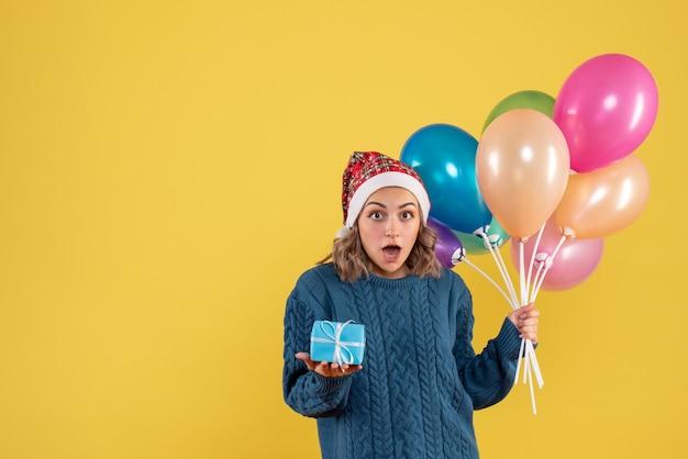 Jeune femme tenant petit cadeau et ballons sur jaune