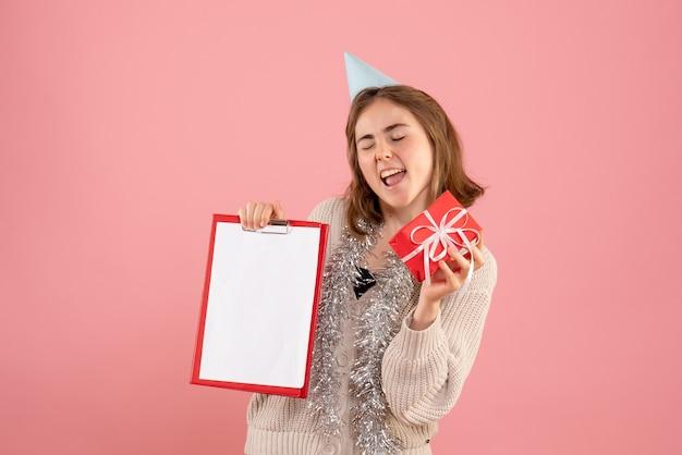 Jeune femme tenant petit cadeau de noël et note sur rose