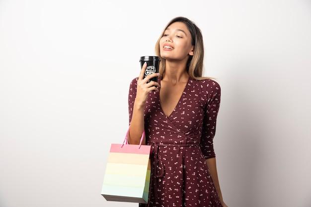 Jeune femme tenant un petit sac de magasin et une tasse de boisson sur un mur blanc.