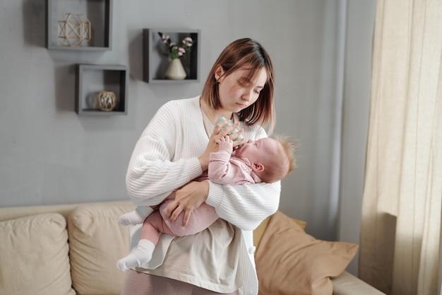 Jeune femme tenant une petite bouteille tout en nourrissant sa petite fille