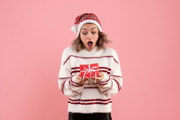 Jeune femme tenant peu de cadeau de noël sur rose
