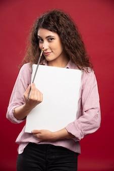 Jeune femme tenant un pinceau et une toile.